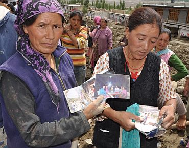 Ladakhi women show photographs of missing relatives in the hope they will be found some day