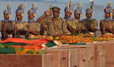 CRPF personnel in New Delhi pay their last respects near the coffins of policemen who died in a Maoist attack in