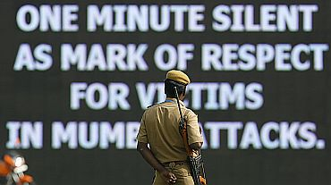 A policeman looks at a message displayed on digital screen during one minute silence for victims of the 26/11 Mumbai attacks