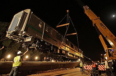 A Delhi Metro rail carriage is lifted on to a track for the trial runs of a new line in New Delhi on June 27, 2010