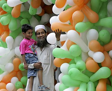 A man shows balloons in the colours of the Indian flag to his child at a market during India's Indep