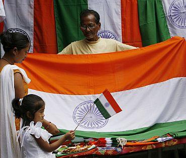 A vender sells Indian national flags to his customers at a shop in Siliguri. National flags are in big demand during Independence Day celebrations