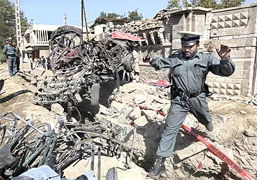 An Afghan policeman jumps over debris at the site of a blast outside the Indian embassy in Kabul
