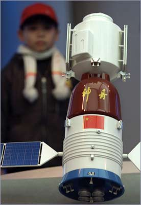 A young boy looks at a model Chinese spaceship displayed at an exhibition center in Shanghai