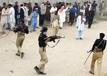A policeman points a gun at an unruly crowd in Pakistan's South Waziristan province