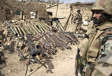 Pakistani soldiers stand next to weapons and ammunition (L) recovered during military operations against Taliban militants in South Waziristan
