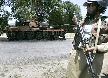 A Pakistani soldier stands guard next to an army tank destroyed by militants in Buner district