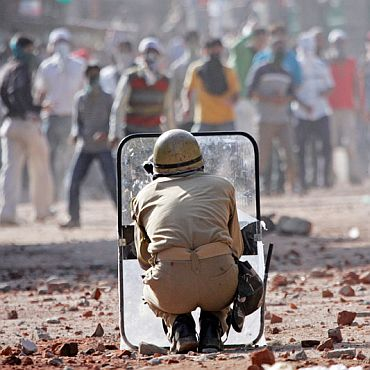 A policeman takes cover as Kashmiri protestors pelt stones