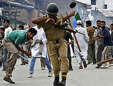 A policeman tries to evade a stone thrown by a protestor