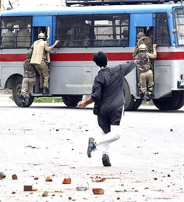 A Kashmiri protestor pelts stones on a bus carrying police personnel