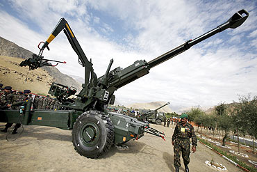 Indian army soldier walks past a Sweden made 155 mm Bofors artillery gun