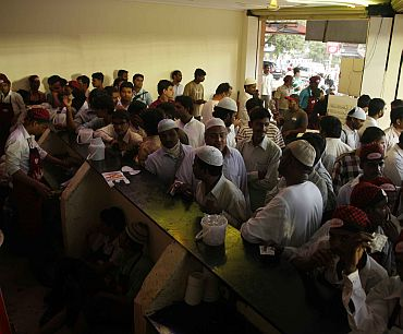People wait at a counter for their Haleem