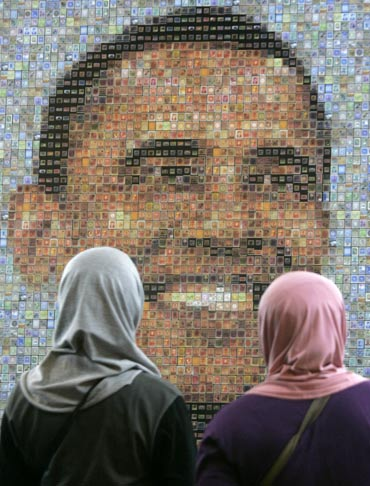 Muslim women look at an image of Barack Obama, made from a mosaic of stamps, in Jakarta