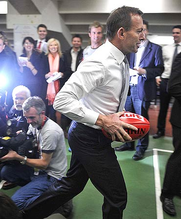 Tony Abbott with an Australian football at the Essendon Football Club