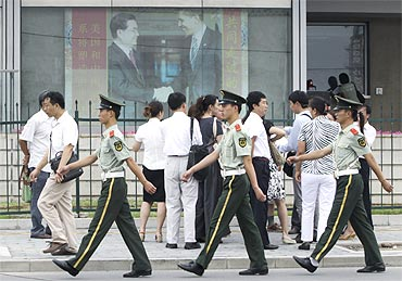 Policemen patrol past a photograph showing China's President Hu Jintao shaking hands with US President Barack Obama