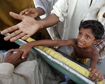 A boy reaches out for relief goods distributed from local residents to flood victims in Muzaffargarh district of Punjab province