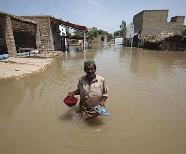 Ali Hassan, a villager, holds his sandals and meal as he wades through floodwaters in Amri village, some 280 km from Karachi