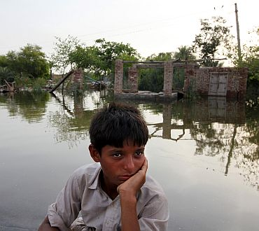 A boy sits in front of a house destroyed by floodwaters in a village in Muzaffargarh district