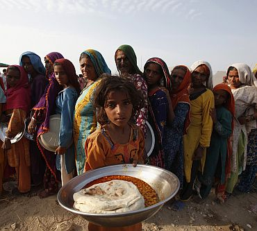 Anila, a flood victim, holds up a plate of food as others queue in a makeshift relief camp in Sukkur, in Sindh province