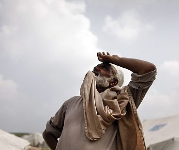 A man looks up as clouds gather over a camp for flood victims near the town of Pir Sabaq in Pakistan's northwest Khyber-Pakhtunkhwa Province