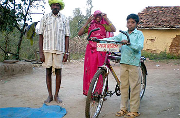 A young village boy prepares to leave for school on his bicycle