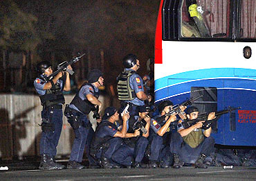 Philippine police take their position during the assault on a bus with tourists being held hostage at Quirino Grandstand in Manila