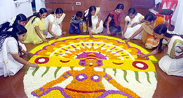 Women decorate with flowers to welcome King Mahabali's revisit during Onam celebrations in Thiruvananthapuram