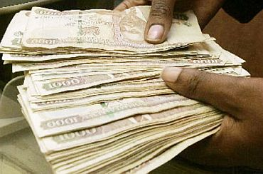 A Kenyan bank staff counts currency