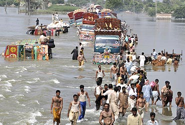 Locals cross a flooded road in Pakistan