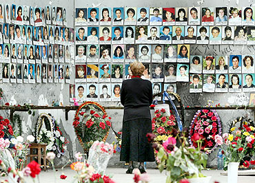 A woman grieves at the wall filled with photographs of the siege victims
