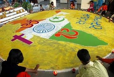 School kids draw a map of India with symbols of Hinduism, Islam, Christianity and Sikhism in Gujarat