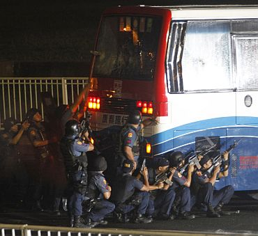 Members of the Philippine National Police Scene of the Crime Operations inspects the damage to the tourist bus