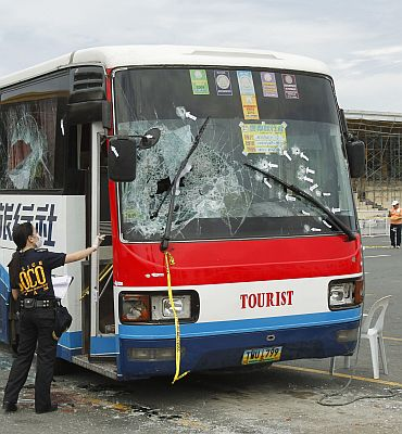 A Scene of the Crime Operations member inspects the damage to the tourist bus