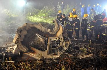 Rescuers check the wreckage of a crashed passenger plane in Yichun, northeast China's Heilongjiang province August 24, 2010