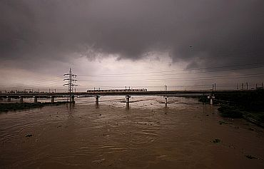 A Metro train moves over a bridge built over the river Yamuna that is over-flowing in New Delhi on Tuesday