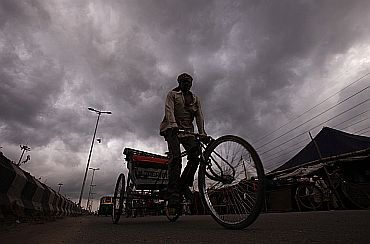 A cycle rickshaw puller is silhouetted against the backdrop of monsoon clouds in New Delhi on Tuesday