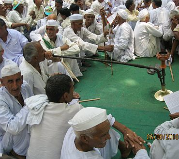 A farmer smokes his hookah as others sit beside him during the protest