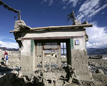 People walk near damaged houses after flash floods occurred on the outskirts of Leh