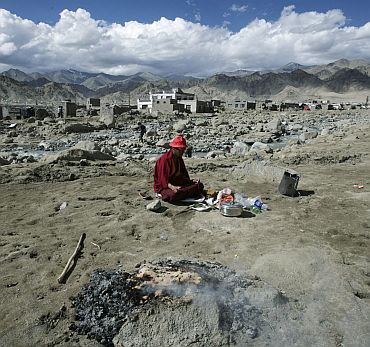 A monk performs religious rites for flash floods victims on the outskirts of Leh
