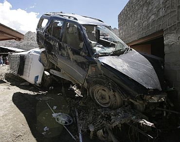 Flash flood victims walk near the wreckage of damaged cars after flash floods in Leh
