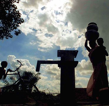 A women carries water pots at a well in a drought hit v