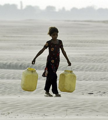 A village girl carries empty containers to collect drinking water near Chilla village in the Bundelkhand region of northern Uttar Pradesh