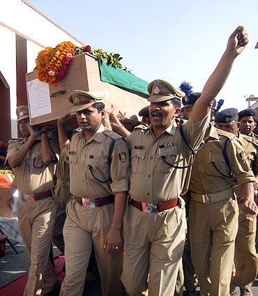 Security personnel carry a coffin of a policeman killed in a Maoist attack in Chhattisgarh
