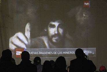 Relatives of the miners trapped underground in a copper and gold mine, gather around a screen that shows the miners inside the mine at Copiapo