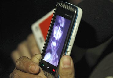 A relative of one of the miners trapped underground in a copper and gold mine, shows a video of a miner on her mobile phone that was recorded from inside the mine in Copiapo