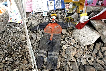A miner's uniform lies on rocks along with letters and pictures to commemorate the 33 miners who are trapped underground