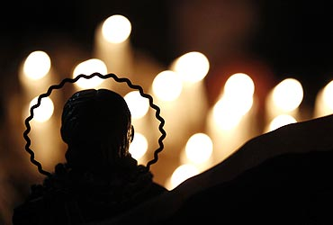 Candles are seen lit behind a religious statue in front of which relatives pray for the 33 miners