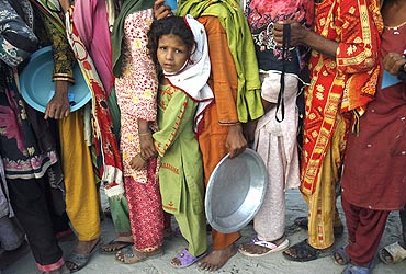 A flood victim stands in queue with others to get food handouts at a relief camp