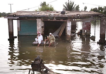 Flood victims sit in front of their destroyed shop in Pakistan's Muzaffargarh district