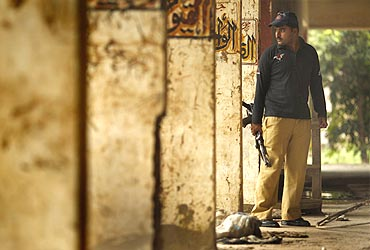 A policeman inspects the flood destroyed police headquarters in Nowshera